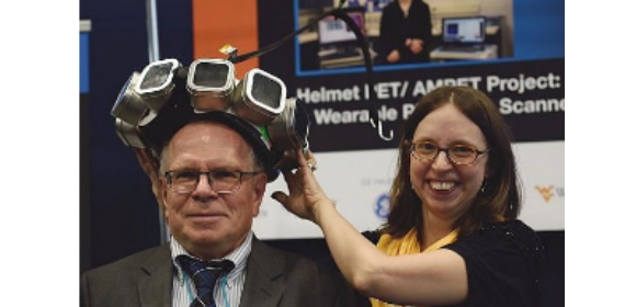 Co-developers Stan Majewski and Julie Brefczynski-Lewis display a mockup of their device at a scientific conference (source: www.bnl.gov).