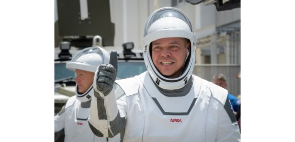 NASA astronauts, Robert Behnken (foreground) & Douglas Hurley, wearing SpaceX spacesuits, as they depart the Neil A Armstrong Operations & Checkout Building for Launch Complex 39A to board the SpaceX Crew Dragon spacecraft for the Demo-2 launch